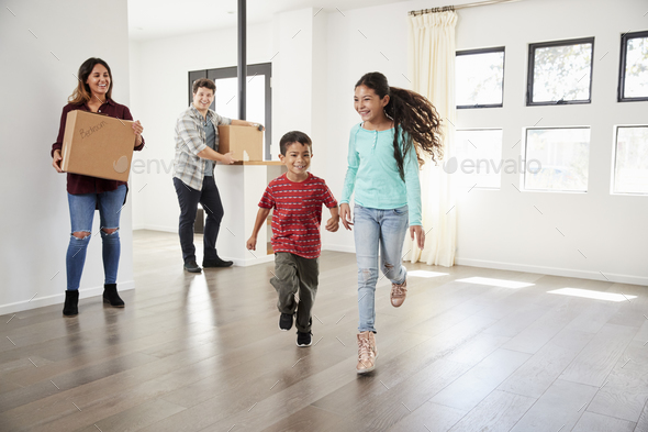 Excited Family Carrying Boxes Into New Home On Moving Day - Stock Photo - Images