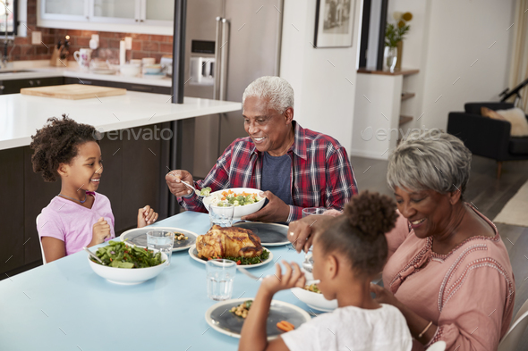 Grandparents Enjoying Meal At Home With Granddaughters - Stock Photo - Images
