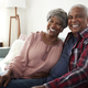 Portrait Of Loving Senior Couple Relaxing On Sofa At Home - PhotoDune Item for Sale