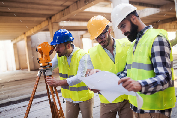 Portrait of construction engineers working on building site - Stock Photo - Images