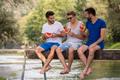 men enjoying watermelon while sitting on the wooden bridge - PhotoDune Item for Sale