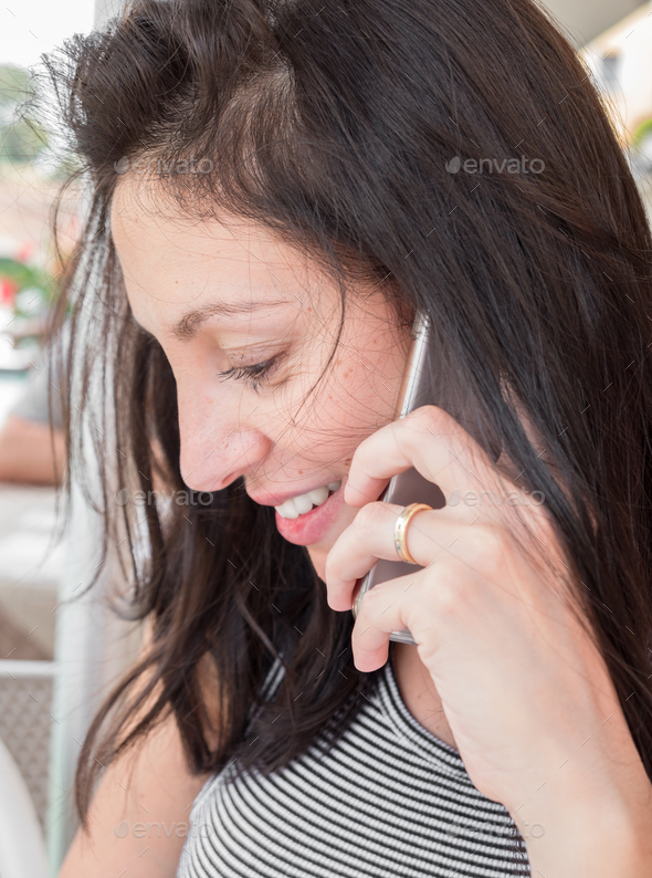 Brunette girl with a striped t-shirt talk on the cell phone - Stock Photo - Images