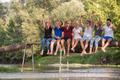 friends enjoying watermelon while sitting on the wooden bridge - PhotoDune Item for Sale