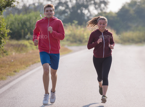 young couple jogging along a country road - Stock Photo - Images