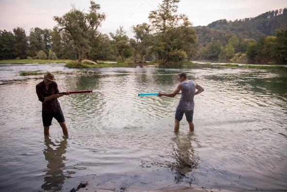 young men having fun with water guns - Stock Photo - Images