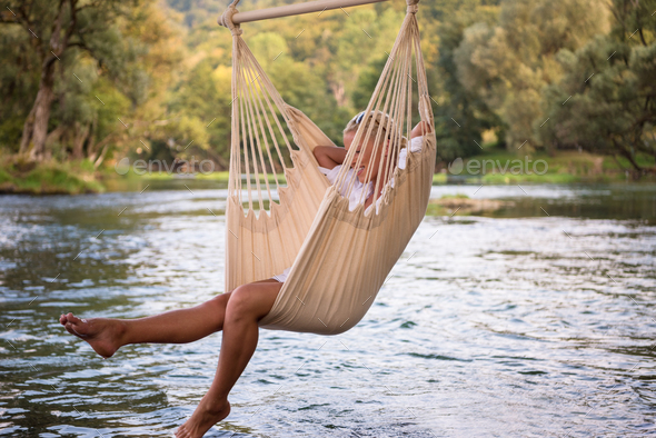 blonde woman resting on hammock - Stock Photo - Images