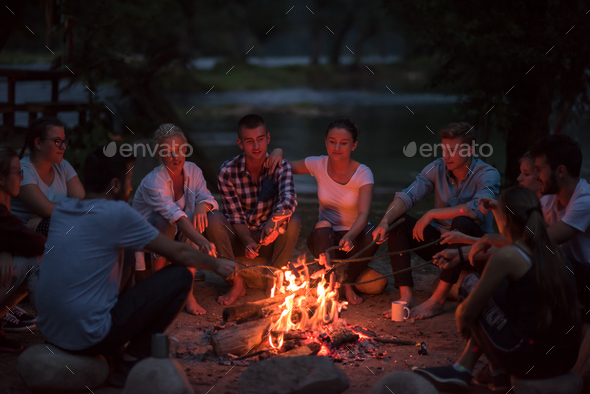 young friends relaxing around campfire - Stock Photo - Images