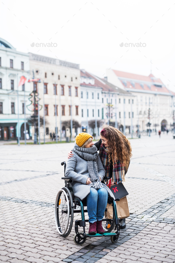 A teenager girl with disabled grandmother in wheelchair outdoors on the street in winter. - Stock Photo - Images