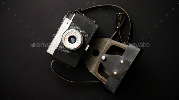 Old retro film camera in leather case on black background - Stock Photo - Images