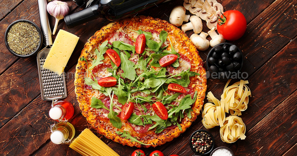 Italian food background with pizza, raw pasta and vegetables on wooden table - Stock Photo - Images