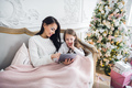 Portrait of smiling little daughter sitting together with her mother and using digital tablet at - PhotoDune Item for Sale