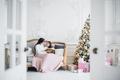 Merry Christmas and Happy Holidays. Pretty young mom reading a book to her cute daughter near - PhotoDune Item for Sale