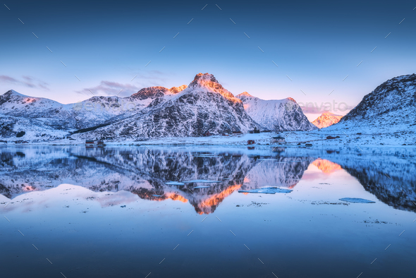 Snowy mountains and colorful sky reflected in water at sunset - Stock Photo - Images