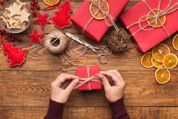 Woman decorating handmade craft Christmas gift boxes - Stock Photo - Images