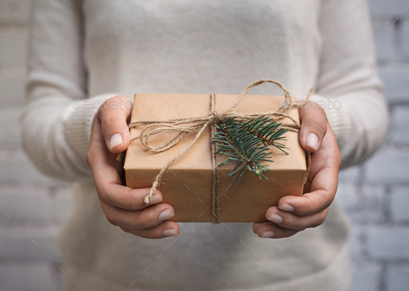 Woman holding craft paper gift box for present - Stock Photo - Images