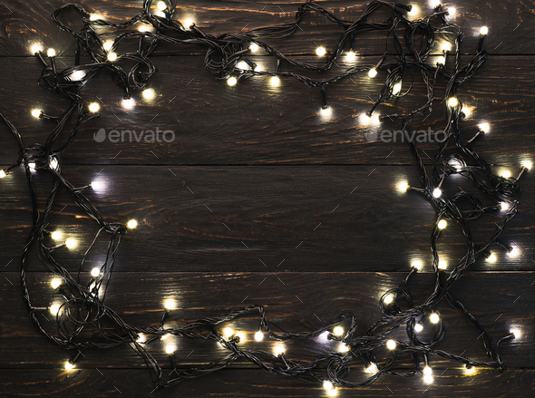Frame of christmas garland lights on wooden background - Stock Photo - Images