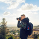 Young photographer with backpack making photos of sea and rocks with the camera. Mediterranean sea - PhotoDune Item for Sale