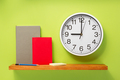 notebook and wall clock on shelf at wall background - PhotoDune Item for Sale