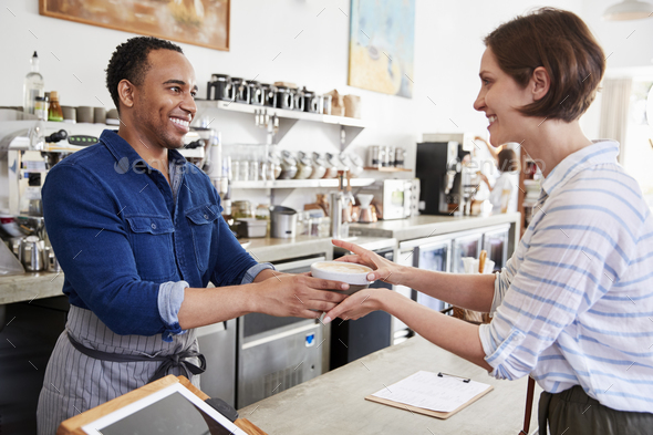Male barista passing coffee to a female coffee shop customer - Stock Photo - Images