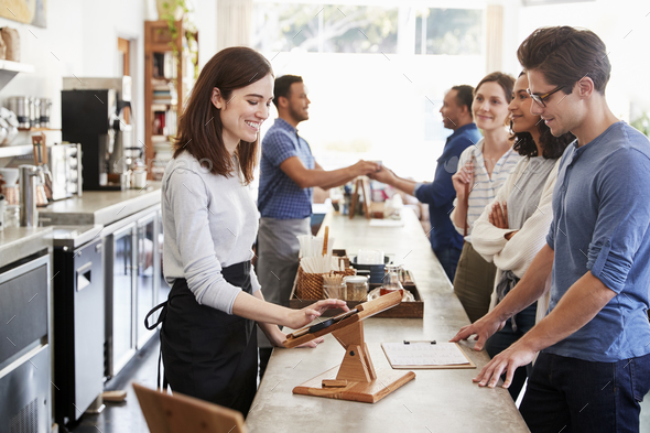 Customers queuing to order and pay at a coffee shop counter - Stock Photo - Images