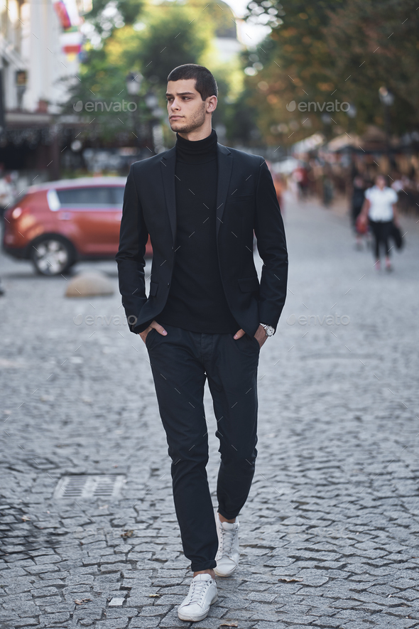 Confident young man walking on a European city street - Stock Photo - Images