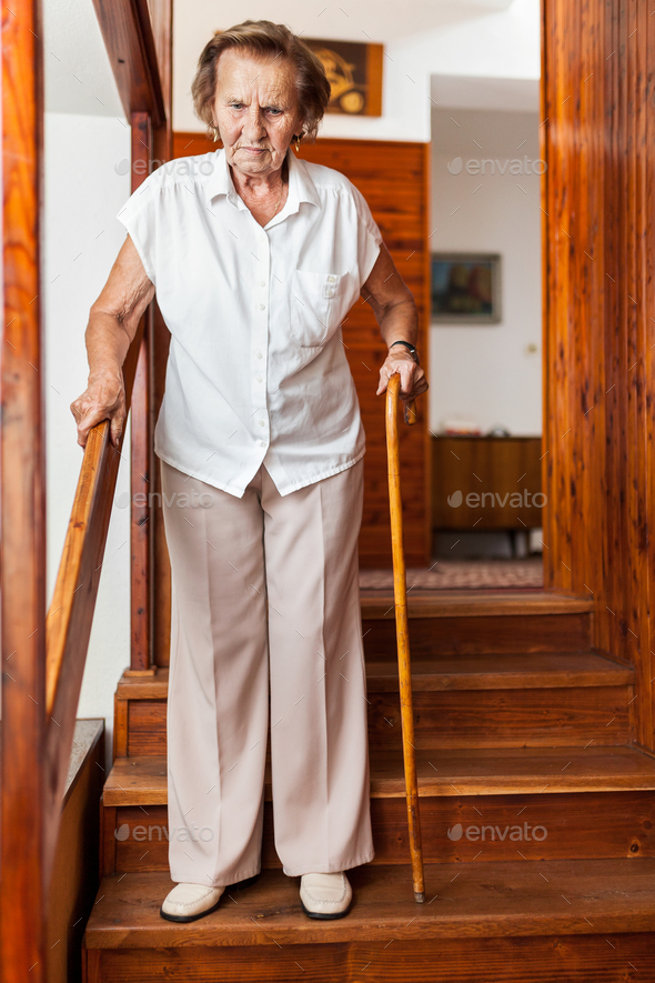Elderly woman at home using a cane to get down the stairs - Stock Photo - Images