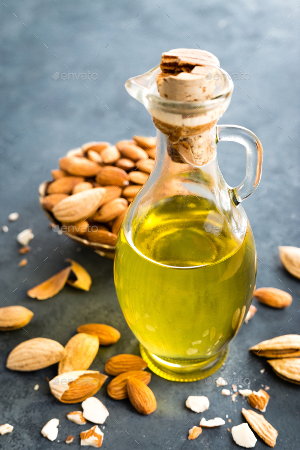Almond oil in glass bottle and almond nuts. Almonds - Stock Photo - Images