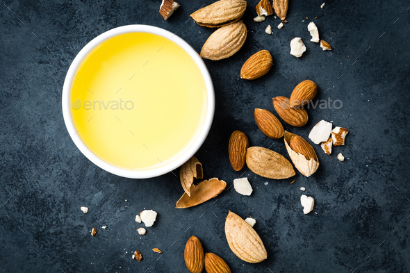 Almond oil in bowl and almond nuts. Almonds - Stock Photo - Images