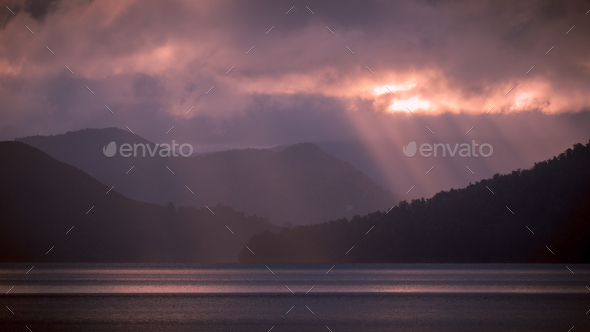 sun through clouds over lake - Stock Photo - Images