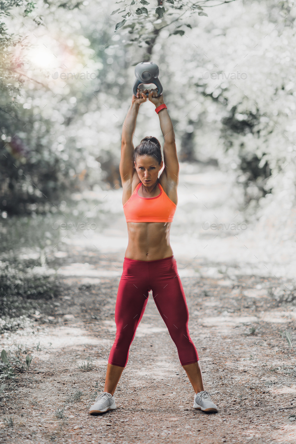 Woman Exercising with Kettlebell Outdoors - Stock Photo - Images