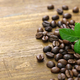 scattered roasted coffee beans and leaves on wooden background - PhotoDune Item for Sale