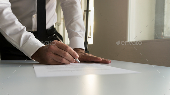 Businessman in office signing contract, document or legal papers - Stock Photo - Images