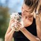 Young smiling woman holding furry baby rabbit - PhotoDune Item for Sale