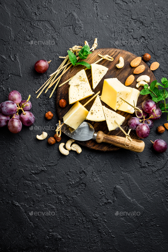 Cheese with grape and nuts on wooden board - Stock Photo - Images