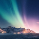 Green and purple aurora borealis over snowy mountains - PhotoDune Item for Sale