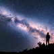 Woman with backpack on the hill against colorful Milky Way - PhotoDune Item for Sale