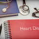 Titled red book Heart Disease along with medical equipment, conceptual image - PhotoDune Item for Sale