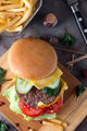 Tasty grilled home made burger cooking with beef, tomato, cheese, cucumber and lettuce. Top view - PhotoDune Item for Sale