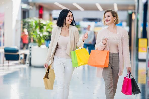 Shopping women talking happy holding shopping bags having fun laughing. Two beautiful young woman - Stock Photo - Images