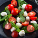 Tasty and beautiful Caprese salad on the black ceramic plate, close up - PhotoDune Item for Sale