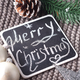 Christmas wishes written in chalk on a blackboard- Happy Christmas on warm scarf and toys - PhotoDune Item for Sale