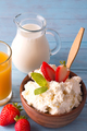 Fresh cottage cheese with strawberries in a wooden bowl with a spoon, glass of milk, jar of juice on - PhotoDune Item for Sale