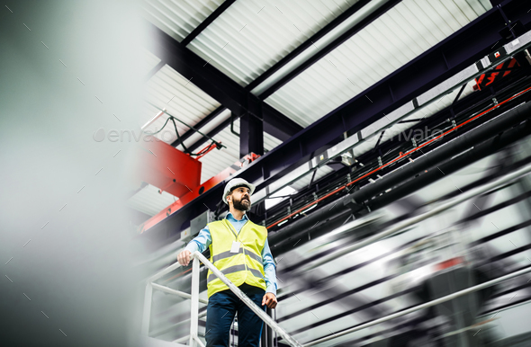 A low angle view of an industrial man engineer standing in a factory. - Stock Photo - Images