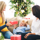 A mother and grandmother giving presents to a small boy at home at Christmas time. - PhotoDune Item for Sale