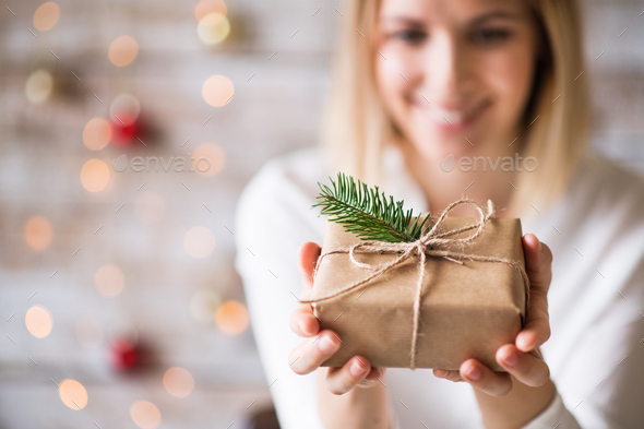 A young woman holding wrapped Christmas present. - Stock Photo - Images