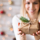 A young woman holding wrapped Christmas present. - PhotoDune Item for Sale