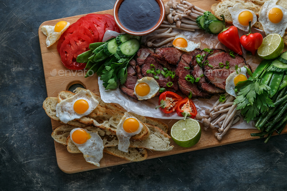 Breakfast meals variety flat lay. Top view on buffet wooden board with meat, eggs, vegetables - Stock Photo - Images