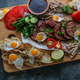 Breakfast meals variety flat lay. Top view on buffet wooden board with meat, eggs, vegetables - PhotoDune Item for Sale