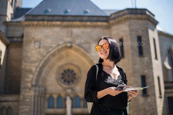 Brunette young woman tourist holding a city map and searching right direction standing outdoors in - Stock Photo - Images
