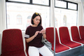 Attractive brunette female tourist travelling by bus using application for navigating in city - PhotoDune Item for Sale